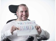Andrew Gurza holding a sign reading #DeliciouslyDisabled